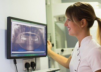Dental assistant looking at x-rays