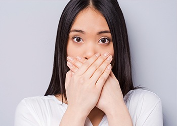 Woman hiding her smile with her hands