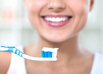 Woman smiling holding a toothbrush with toothpaste